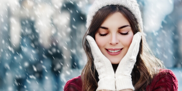 A woman touching her face with her hands during the Winter.
