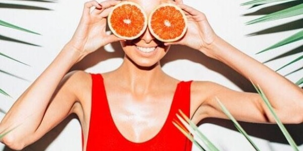 A woman holding oranges over her eyes.